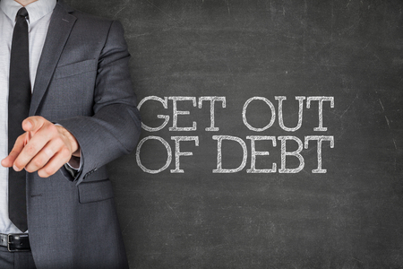 dues: Get out of debt on blackboard with businessman finger pointing Stock Photo