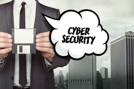cyber defence: cyber security text on speech bubble with businessman holding diskette on cityscape background