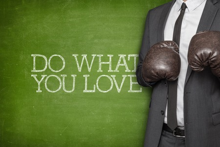 Do what you love on blackboard with businessman wearing boxing gloves