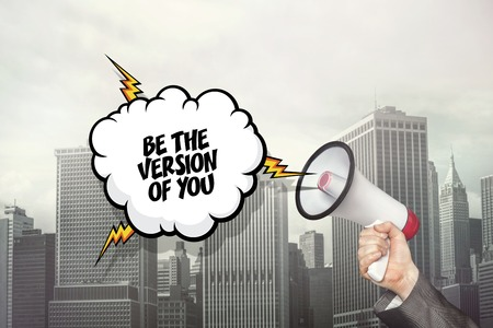 kind: Be the version of you text on speech bubble and businessman hand holding megaphone on city background Stock Photo