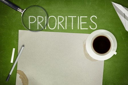 priorities: Priorities concept on green blackboard with empty paper sheet Stock Photo