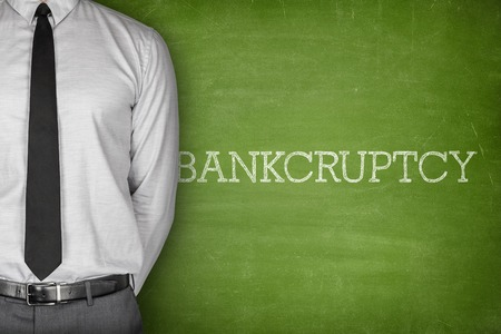 liquidate: Bankcruptcy on blackboard with businessman in a suit on side