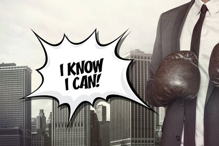 text bubble: I know I can text on speech bubble with businessman wearing boxing gloves on city background