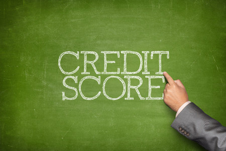 Credit score text on blackboard with businessman hand pointing