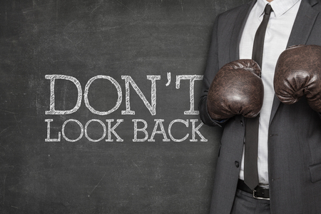 business suit: Dont look back on blackboard with businessman wearing boxing gloves