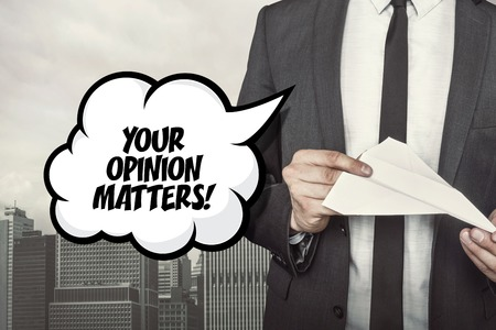 opinion: Your opinion matters text on speech bubble with businessman holding paper plane in hand on city background Stock Photo