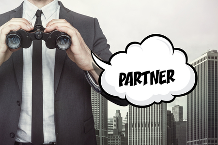 estimating: Partner text on speech bubble with businessman holding binoculars on city background Stock Photo