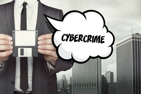 office theft: Cybercrime text on speech bubble with businessman holding diskette on cityscape background