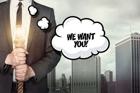 staffing: We want you text on speech bubble with businessman holding lamp on city background