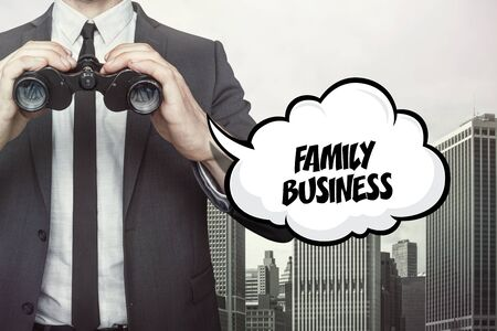 Family business text on speech bubble with businessman holding binoculars on city background