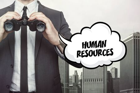 estimating: Human resources text on speech bubble with businessman holding binoculars on city background Stock Photo