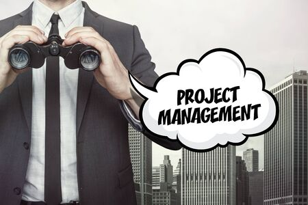 estimating: Project management text on speech bubble with businessman holding binoculars on city background