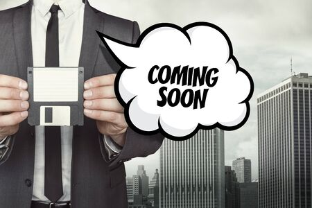 Coming soon text on speech bubble with businessman holding diskette on cityscape background
