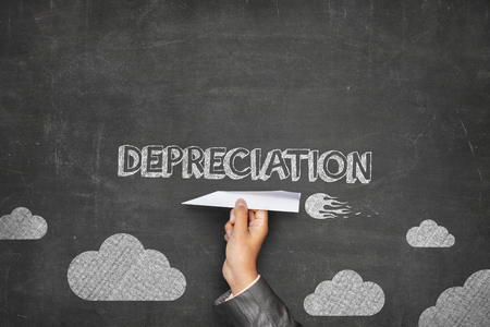 demotion: Depreciation concept on green blackboard with businessman hand holding paper plane