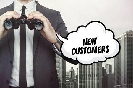 businessman cartoon: New customers text on speech bubble with businessman holding binoculars on city background Stock Photo