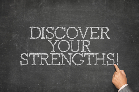 Discover your strengths text on blackboard with businessman hand pointing
