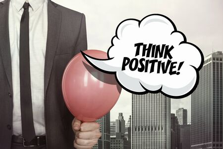 assured: Think positive text on speech bubble with businessman holding balloon on cityscape background Stock Photo