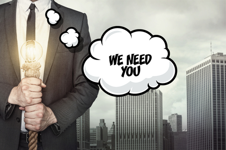 staffing: We need you text on speech bubble with businessman holding lamp on city background