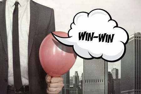 constructive: Win win text on speech bubble with businessman holding balloon on cityscape background
