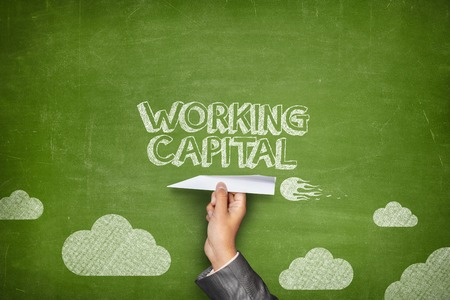 Working capital concept on green blackboard with businessman hand holding paper plane 免版税图像