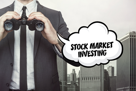 foretelling: Stock market investing text on speech bubble with businessman holding binoculars on city background