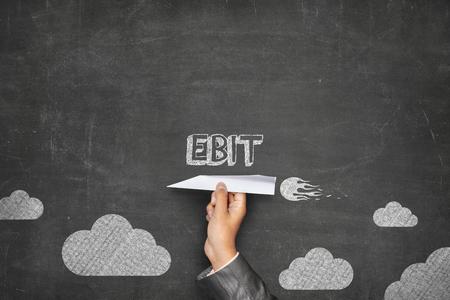 threw: EBIT concept on black blackboard with businessman hand holding paper plane