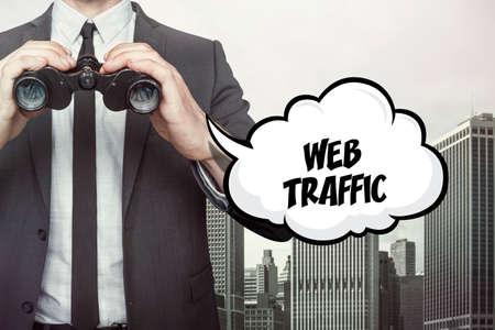 web traffic: Web traffic text on speech bubble with businessman holding binoculars on city background