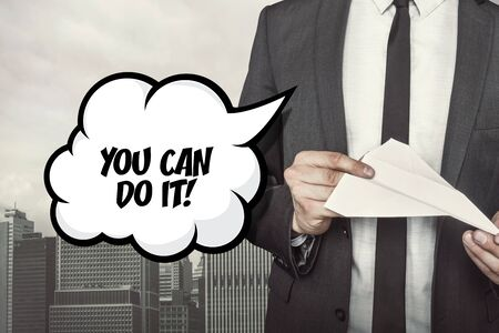 都市の背景に手で紙飛行機を持って実業家と吹き出しのテキスト行うことができます。