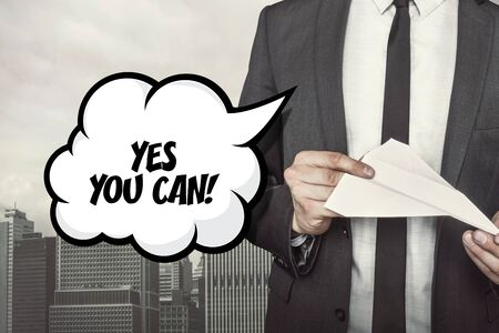 can yes you can: Yes you can text on speech bubble with businessman holding paper plane in hand on city background