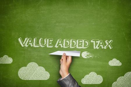 Die Mehrwertsteuer-Konzept auf der grünen Tafel mit Geschäftsmann Hand hält Papierflugzeug