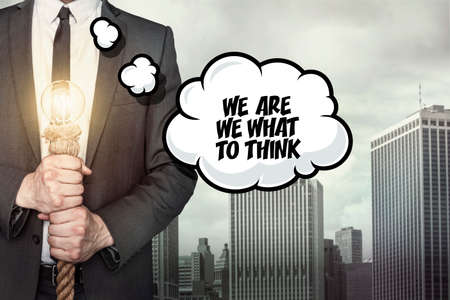 considerate: We are we what to think text on speech bubble with businessman holding lamp on city background