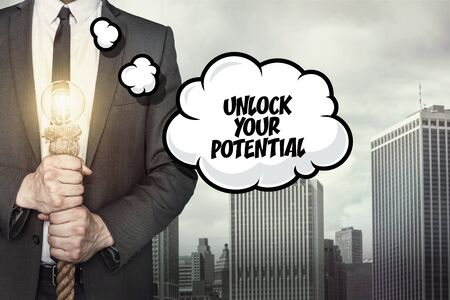 potential: Unlock your potential text on speech bubble with businessman holding lamp on city background