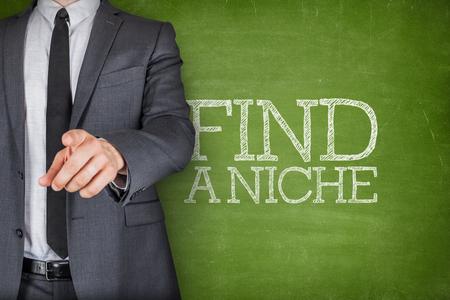 conclusion: Encuentre un nicho en la pizarra con el dedo del hombre de negocios apuntando