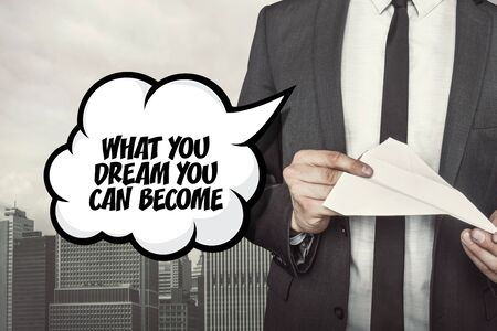 become: What you dream you can become text on speech bubble with businessman holding paper plane in hand on city background