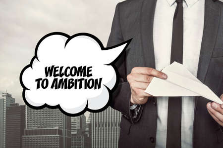 ambition: Welcome to ambition text on speech bubble with businessman holding paper plane in hand on city background Stock Photo