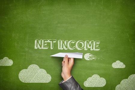 net income: Net income concept on green blackboard with businessman hand holding paper plane