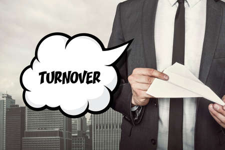 replacing: Turnover text on speech bubble with businessman holding paper plane in hand on city background Stock Photo