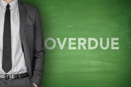 net income: Overdue text on green blackboard with businessman Stock Photo