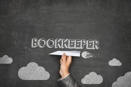 threw: Bookkeeper concept on black blackboard with businessman hand holding paper plane Stock Photo