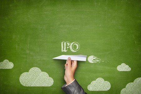 initial public offerings: IPO concept on green blackboard with businessman hand holding paper plane Stock Photo