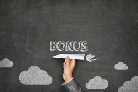 inducement: Bonus concept on black blackboard with businessman hand holding paper plane Stock Photo