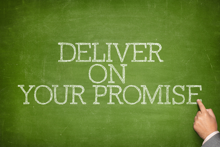 deliver: Deliver on your promise text on blackboard with businessman hand pointing