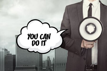 you can do it: You can do it text on speech bubble with businessman and megaphone on city background