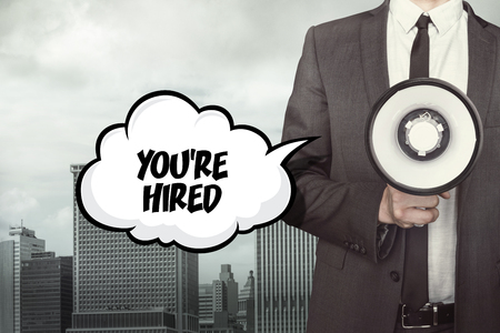 appointed: Youre hired text on speech bubble with businessman and megaphone on city background