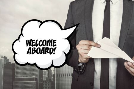 Welcome aboard text on speech bubble with businessman holding paper plane in hand on city background