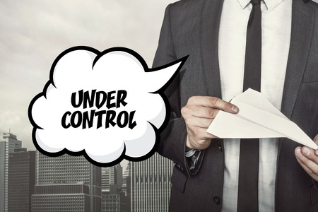 under control: Under control text on speech bubble with businessman holding paper plane in hand on city background
