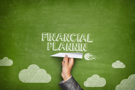 project planning: Financial planning concept on green blackboard with businessman hand holding paper plane