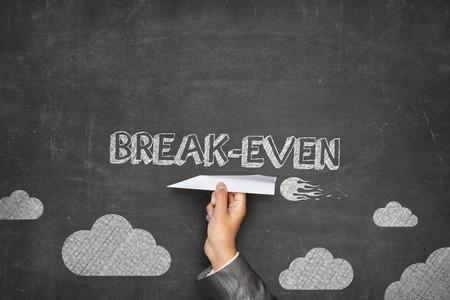 threw: Break-even concept on black blackboard with businessman hand holding paper plane
