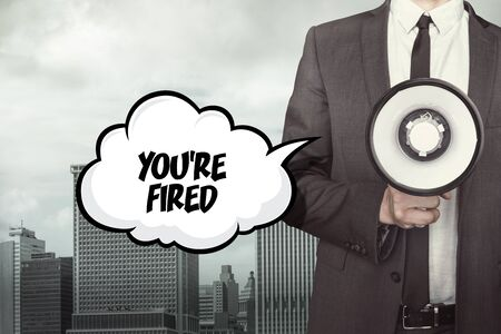 unemployed dismissed: Youre fired text on speech bubble with businessman and megaphone on city background