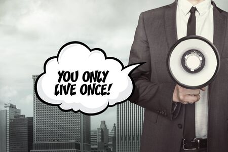 once: You only live once text on speech bubble with businessman and megaphone on city background Stock Photo